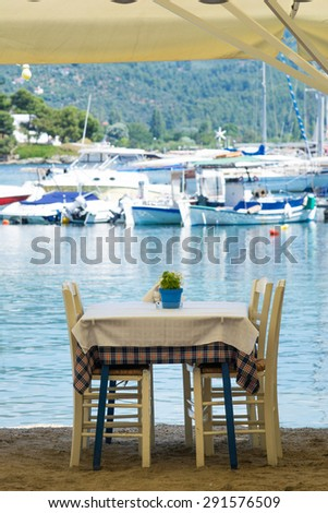 Chairs and table under large parasol on a sandy beach with blurred boats and ships in a background - stock photo
