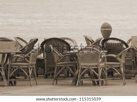 Chairs and tables in a cafe near the sea (in sepia, retro style) - stock photo