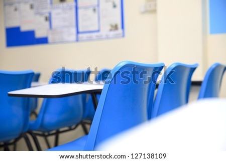 Chairs and tables in a classroom - stock photo