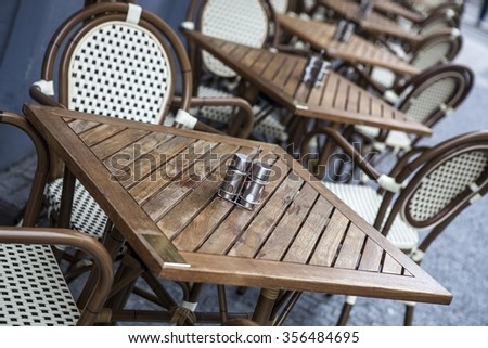 Chairs and tables in outdoors caffe on day - stock photo