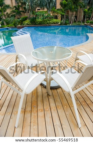 chairs and tables next to a swimming pool. - stock photo