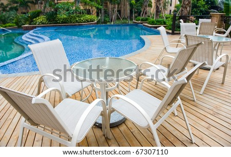 chairs and tables next to a swimming pool.