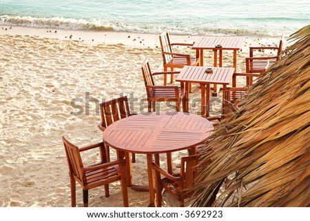 Chairs and tables of outdoor coffee shop on the beach next to sea in Antibes, France