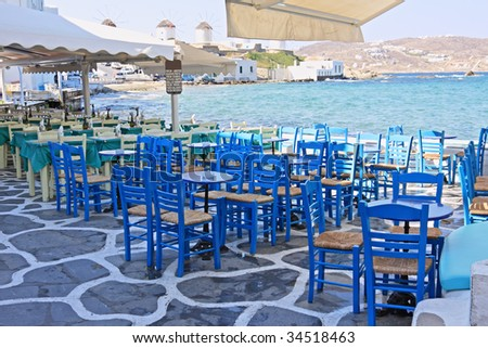 """Chairs and tables of restaurants in the area of """"Little Venice"""" in Mykonos island, Greece - stock photo"""