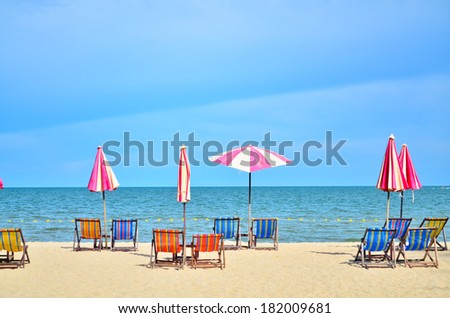 Chairs and umbellar on white sand beach. - stock photo