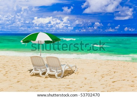 Chairs and umbrella at tropical beach - vacations background - stock photo