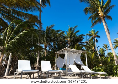 Chairs and umbrella on a beach with shadow from palm tree - stock photo