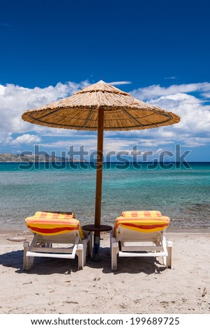 Chairs and umbrella on a beautiful beach. - stock photo