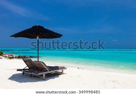 Chairs and umbrella on a beautiful tropical beach at Maldives - stock photo