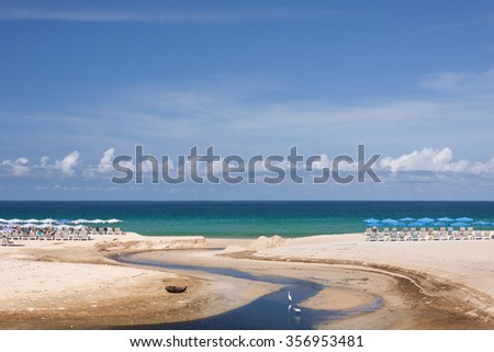 Chairs and umbrella on a beautiful tropical beach with canal - stock photo