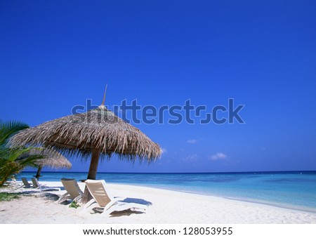chairs and umbrella on a sand beach - stock photo