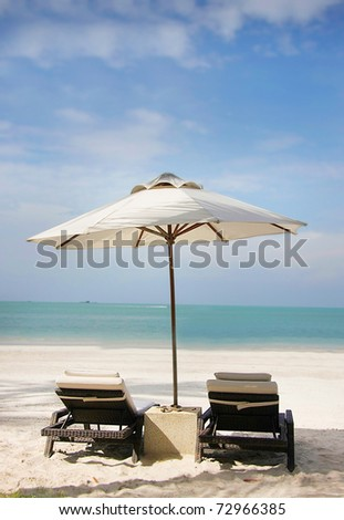 chairs and umbrella on sand beach - stock photo