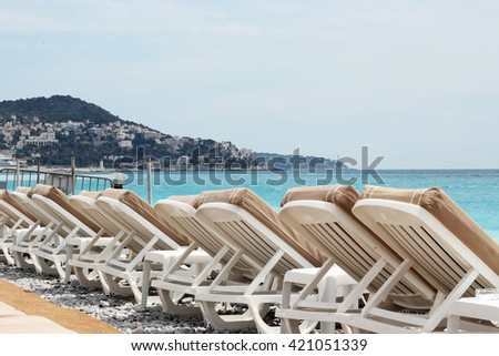 Chairs and umbrellas on Nice beach, luxury view, summer vacation outdoor - stock photo