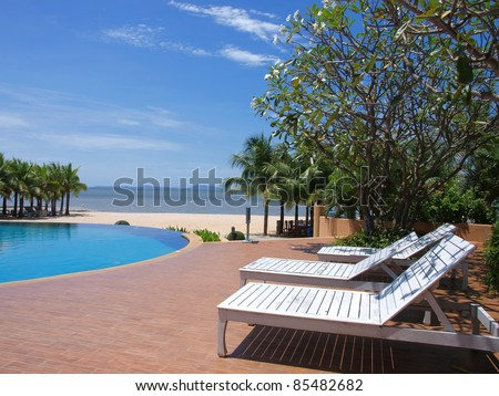 chairs around swimming pool near the beach - stock photo