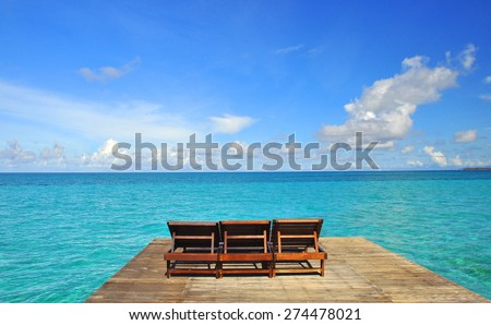 Chairs at beauty seascape under blue clouds sky - stock photo