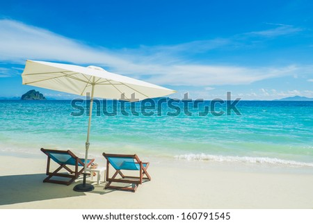 chairs at the beach in Thailand with umbrella - stock photo