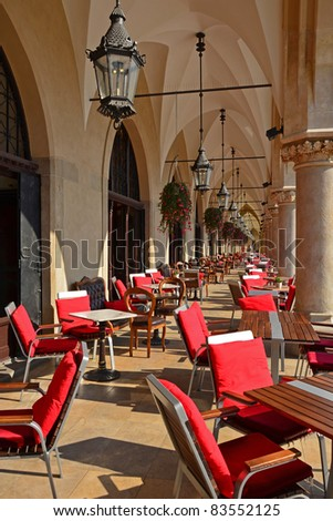 Chairs in local cafe in Sukiennice building in Krakow - stock photo