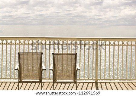 Chairs on a balcony with an ocean view - stock photo