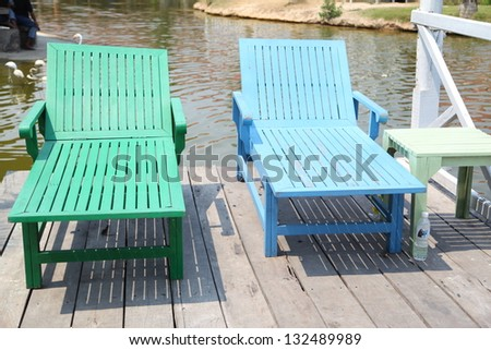 chairs on a beach with beautiful view on a lake - stock photo