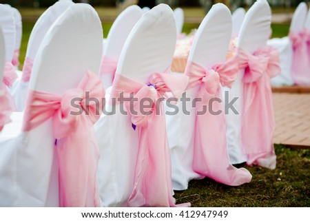 chairs on a wedding ceremony decorated with white textile and pink bows - stock photo