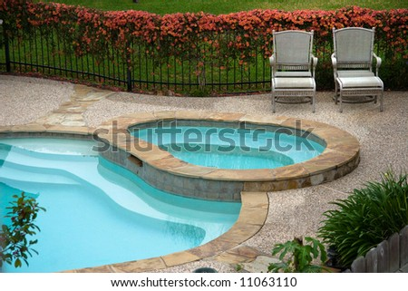 Chairs on deck besides swimming pool in back yard - stock photo