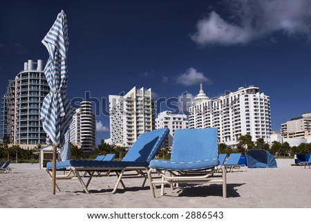 Chairs on the empty beach. South Beach (Miami) hotels in the background - stock photo
