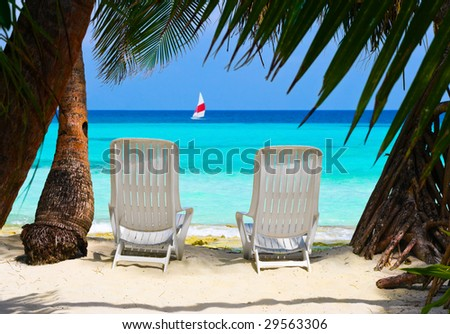Chairs on tropical beach - abstract vacation background - stock photo