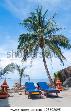 chairs on tropical beach with palm tree - stock photo
