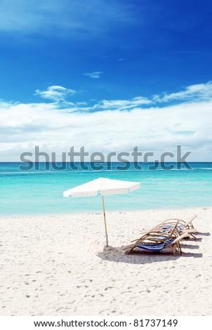 Chairs on white sand beach. - stock photo