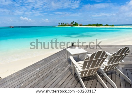 chairs on wooden deck towards the sea in maldives island resort - stock photo
