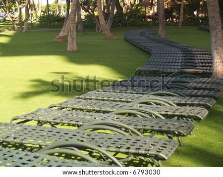 chairs under sun on a green beachr - stock photo
