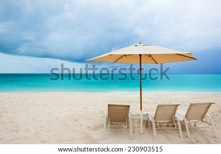 Chairs under umbrella on a stunning Caribbean beach