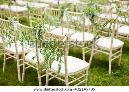 chairs with garland of eucalyptus on wedding ceremony - stock photo