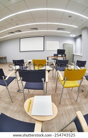 Chairs with notepads in an empty classroom. Fisheye photo - stock photo