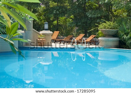 chaise longue and swimming-pool - stock photo
