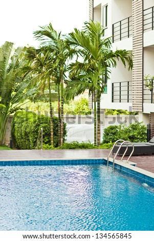 chaise longue and swimming pool in a hotel - stock photo