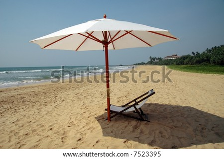 chaise longue and umbrella at the beach - stock photo