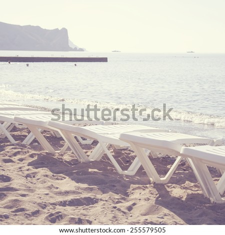 Chaise-longue stands on beach.Special toned photo in vintage style - stock photo