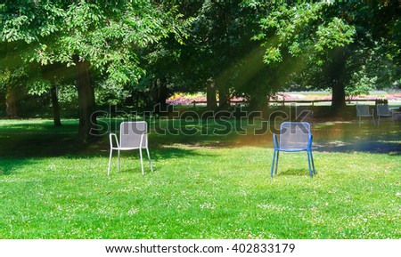 Chaise lounge for relaxing on a green meadow.Watering the lawn in the city park. - stock photo