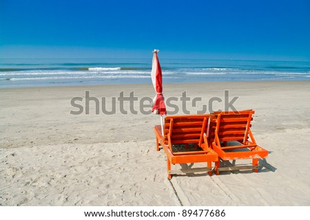 Chaise lounges on an ocean coast - stock photo