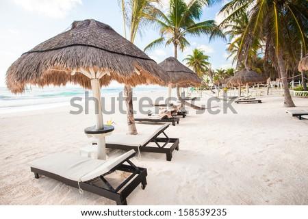 Chaise lounges under an umbrella on sandy beach - stock photo
