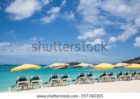 Chaise Lounges with Sun Umbrellas on a Beautiful Tropical Beach