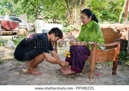CHAIYAPHUM, THAILAND - APRIL 13: Thai people celebrate Songkran (new year / water festival: 13 April) by giving garlands to their seniors and asked for blessings on April 13, 2012 in Chaiyaphum, Thailand. - stock photo
