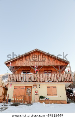 Chalet with christmas decoration on snowy mountain under blue sky - stock photo