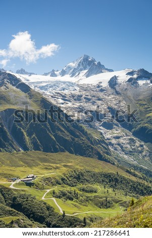Chalets at the bottom of massive Tour Glaciers, in France. - stock photo