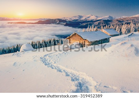 chalets in the mountains at sunset - stock photo