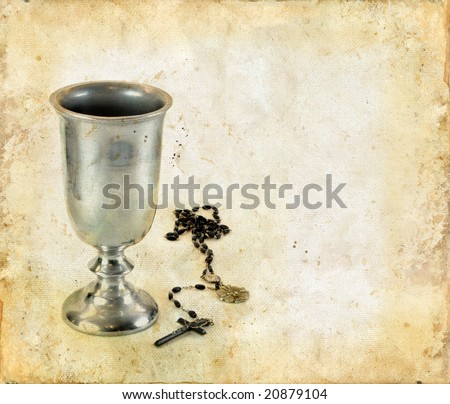 Chalice for communion and a rosary on a grunge background.