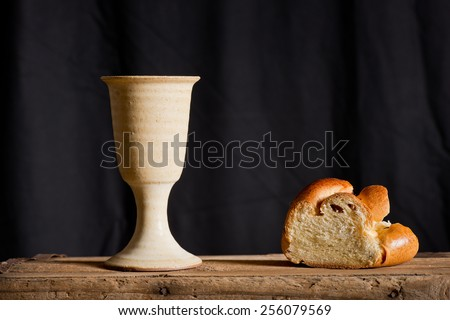 chalice of wine and bread on the dark background - stock photo
