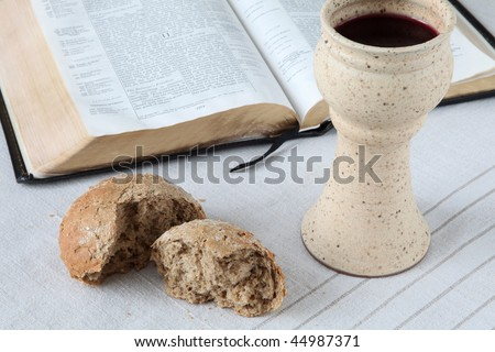 Chalice with red wine, bread and Holy Bible - stock photo