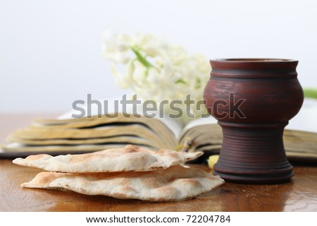 Chalice with red wine, pita bread, Holy Bible and white hyacinth - stock photo